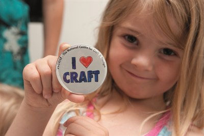 "A child holding up an ""I love craft"" badge"